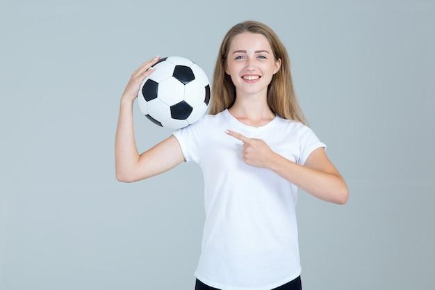 La giovane donna felice con un pallone da calcio in sue mani indica il lato su gray