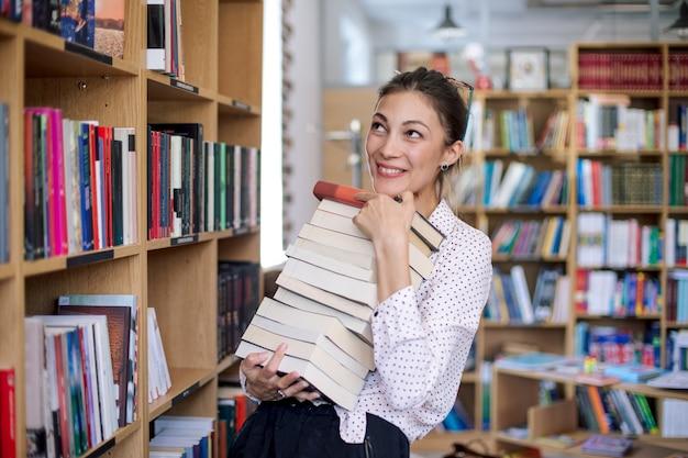 Giovane donna felice con una pila di libri in biblioteca
