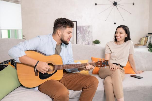 Felice giovane donna con un sorriso a trentadue denti seduta sul divano in soggiorno e guardando suo marito che suona la chitarra e canta per lei