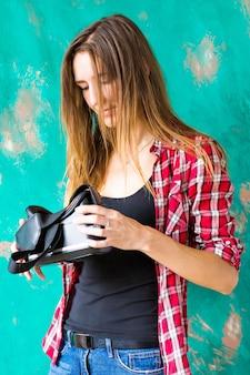 Felice giovane donna con auricolare per realtà virtuale o occhiali 3d e cuffie