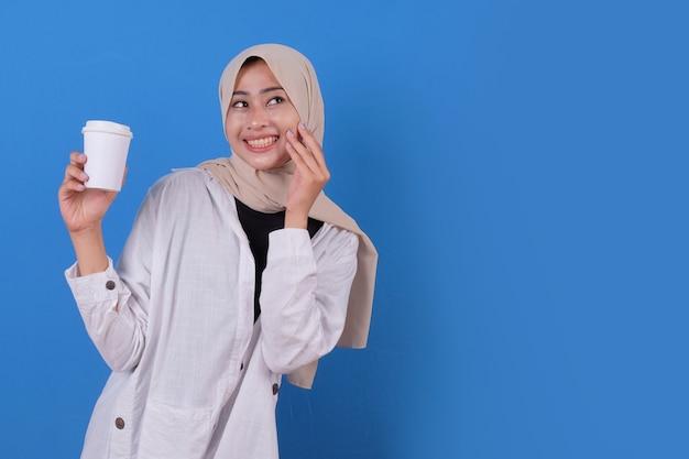 Felice di giovane donna con camicia bianca e velo da portare che tiene tazza di caffè