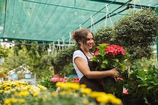 Felice giovane donna che lavora in una serra