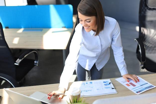 Felice giovane donna che scrive qualcosa mentre si lavora in ufficio.