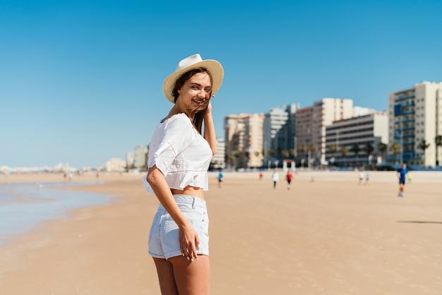 Felice giovane donna wtands sulla spiaggia nel periodo estivo