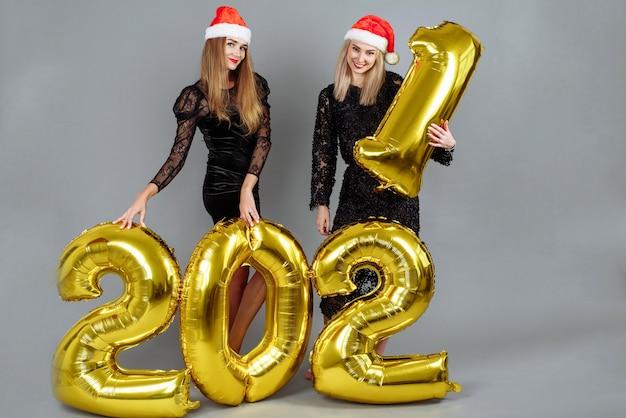 Giovani donne felici in cappelli di natale che tengono palloncini oro 2021