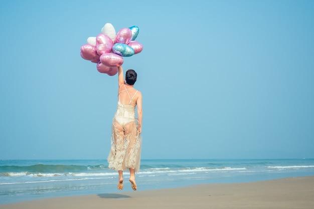 Esistono donne felici e giovani con i capelli corti che reggono mongolfiere più luminose e brillanti. palline luminose nelle mani di una ragazza che riposa sulla spiaggia.