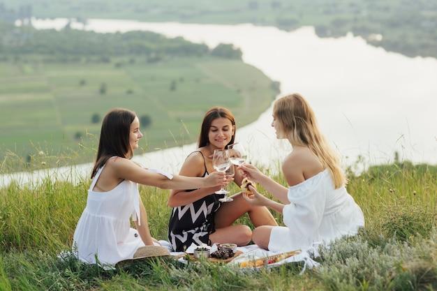 Amici felici delle giovani donne che fanno un brindisi con vino bianco. godersi il picnic sulla collina.