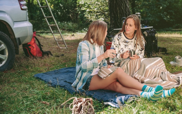 Felici giovani amiche che parlano e riposano sedute sotto una coperta in campeggio nella foresta