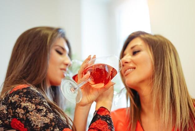 Giovani donne felici divertendosi bevendo vino a casa