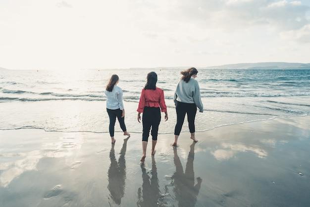 Giovani donne felici che ridono e sorridono in spiaggia in una giornata estiva, godendosi le vacanze, concetto di amicizia che si gode l'aria aperta