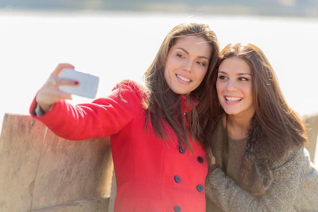 Giovani donne felici che prendono foto con il telefono cellulare