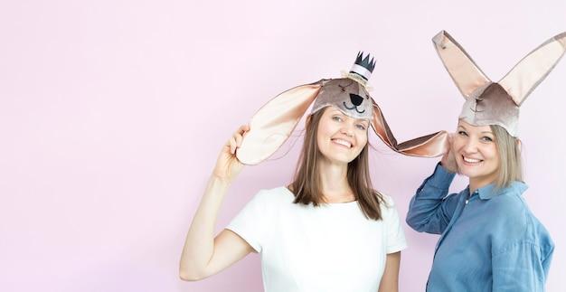 Giovani donne felici che indossano orecchie da coniglio che giocano con loro su sfondo rosa chiaro