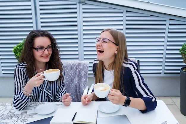 Giovani donne felici con un laptop che sorridono e usano un laptop moderno per studiare seduti su sedie in un accogliente caffè all'aperto