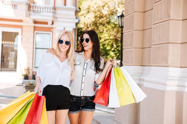 Giovani donne felici con i sacchetti della spesa che camminano lungo la via della città