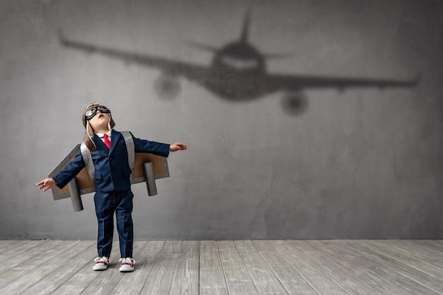 Il bambino hapy vuole diventare un pilota. il bambino divertente sogna di diventare un aviatore.