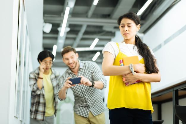 Molestie. giovane ragazza nervosa che cammina all'università e si sente molestata dai suoi compagni studenti mentre li sente urlare e scattare foto del suo corpo