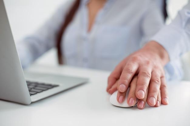 Vittima di molestie. primo piano di una mano maschile che viene messa sulla mano femminile mentre la molesta