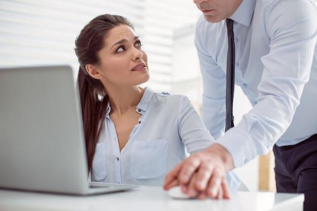 Molestie sul lavoro. infelice bella giovane donna seduta al tavolo e guardando il suo capo mentre viene molestata sessualmente