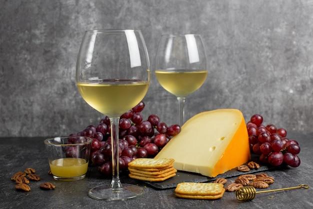 Gouda di formaggio a pasta dura con uva, noci, miele e cracker e due bicchieri di vino bianco su uno sfondo di cemento scuro.