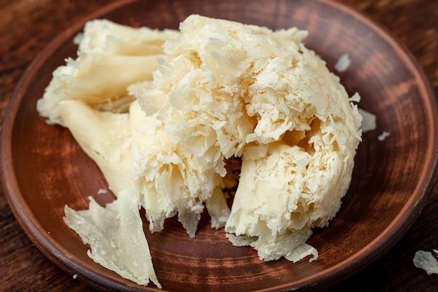 Patatine a fette di formaggio duro su un piatto di argilla su uno sfondo di legno