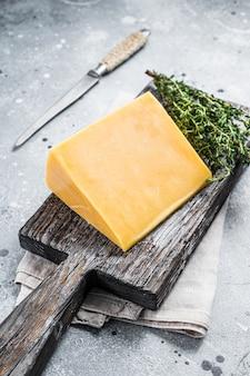 Formaggio a pasta dura con coltello su tagliere di legno. parmigiano. sfondo grigio. vista dall'alto.