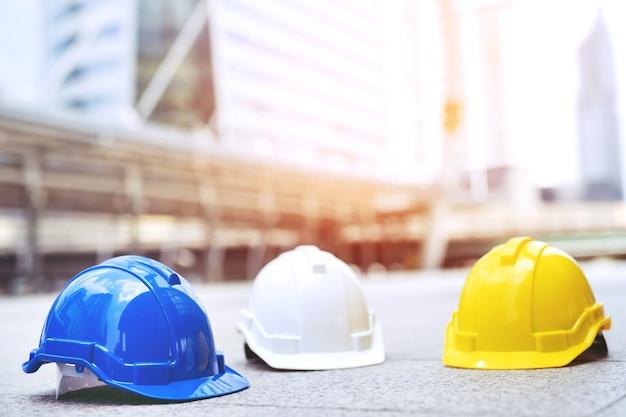 Cappello di casco di usura di sicurezza dura nel progetto al cantiere edile sul pavimento di cemento sulla città.