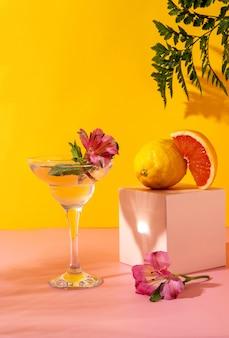 Cocktail di seltz duro con aromi di frutti di bosco guarnito con fiori di alstroemeria. bevanda estiva colorata rinfrescante su sfondo giallo con felce ombra.