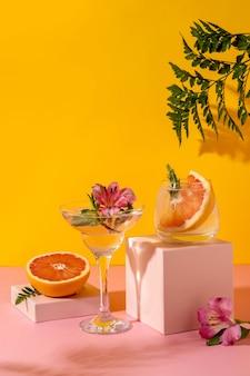 Cocktail di seltz duro con aromi di frutti di bosco guarniti con fiori di alstroemeria. bevanda estiva colorata rinfrescante su sfondo giallo con felce ombra.