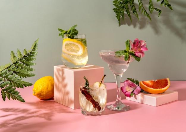 Cocktail hard seltz con vari frutti: pera, pompelmo, limone. bevande estive colorate rinfrescanti su sfondo verde con felce ombra.