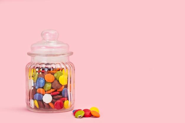 Caramelle di cioccolato a guscio duro in un barattolo di cristallo e su uno sfondo rosa con spazio di copia