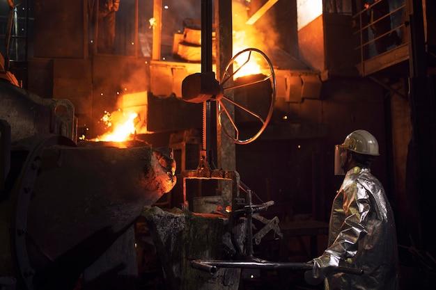 Duro lavoro in fonderia e fusione del ferro in fornace.