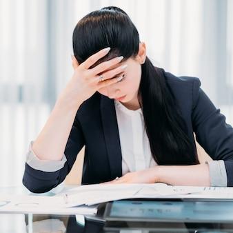 Giornata lavorativa dura in ufficio. donna stanca di affari alla sua scrivania