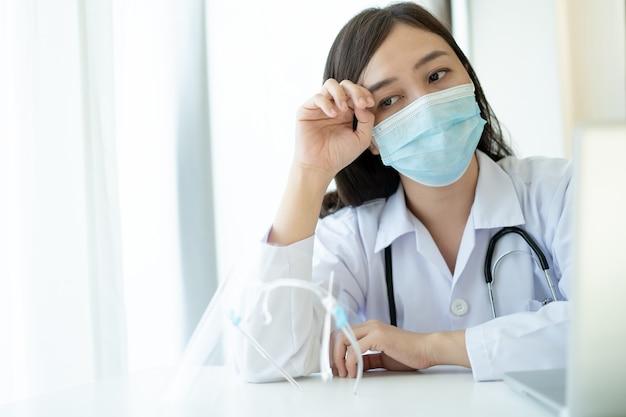 Duro lavoro di una giovane dottoressa asiatica in ospedale, stressante - operatore sanitario maniaco del lavoro in ospedale. farmaco che lavora stanco per il duro lavoro.
