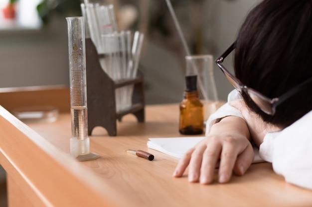 La donna stanca che lavora sodo in camice bianco si è addormentata al lavoro nel laboratorio di ricerca