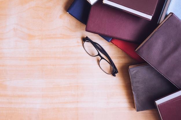 Libri con copertina rigida con occhiali sulla tavola di legno. spazio libero per il testo
