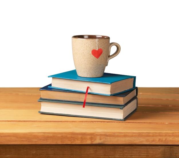 Libri con copertina rigida e tazza a forma di cuore su tavola di legno