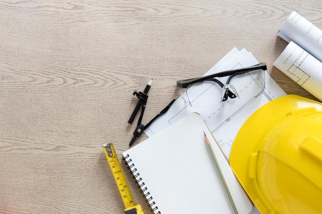 Elmetto protettivo e materiale da disegno sul ripiano del tavolo in legno
