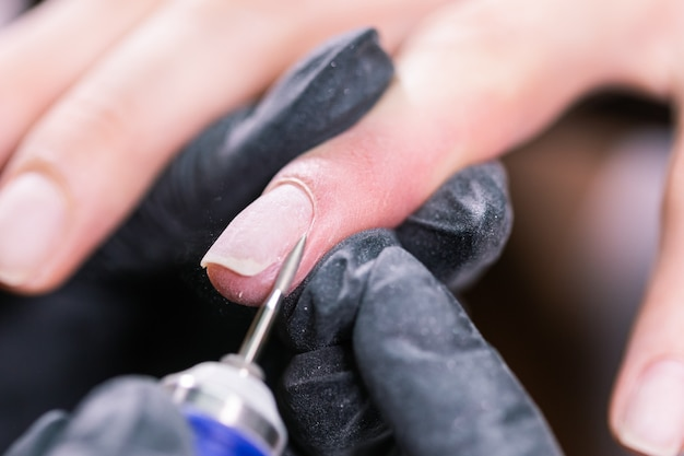 Manicure hardware in un salone di bellezza. manicure femminile sta applicando trapano elettrico per unghie