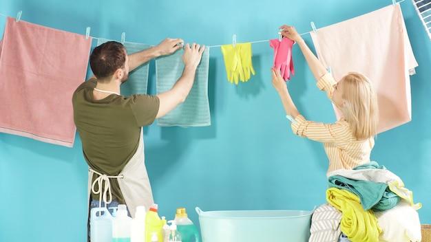 Coppia di uomini e donne laboriosi sono pronti ad aiutarti con il tuo bucato. servizio di lavanderia