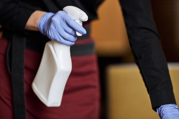 Squadra laboriosa che disinfetta le aree frequentemente toccate con disinfettante