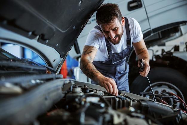 Impiegato barbuto dedito laborioso in tuta che fissa il motore. in fondo è il camion. concetto di lavori manuali.