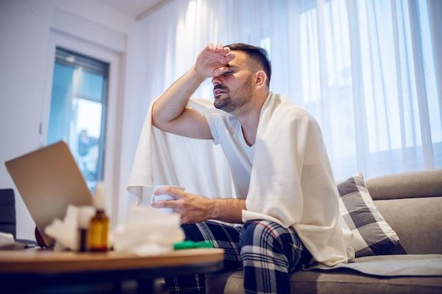 Impiegato laborioso in pigiama e coperto di coperta con febbre.