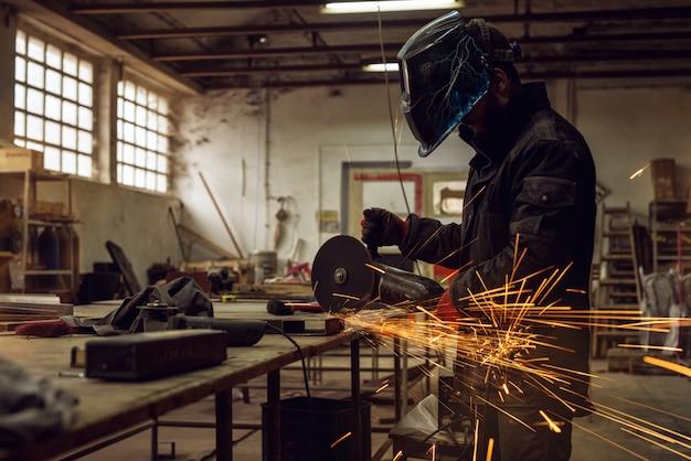 Uomo laborioso con maschera di protezione che lavora con lo strumento smerigliatrice elettrica sulla struttura in acciaio in fabbrica mentre scintille volanti