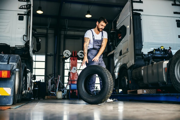 Meccanico laborioso che rotola pneumatico per cambiarlo su camion. è in garage di ditta di import ed export.