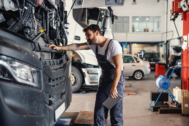Meccanico barbuto tatuato laborioso che si appoggia al camion e controlla il motore mentre si trova nel garage della ditta di importazione ed esportazione.