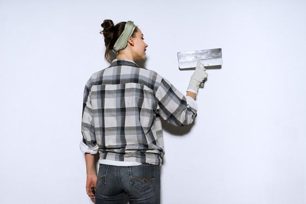 La laboriosa pittrice-costruttrice allinea le pareti con una spatola