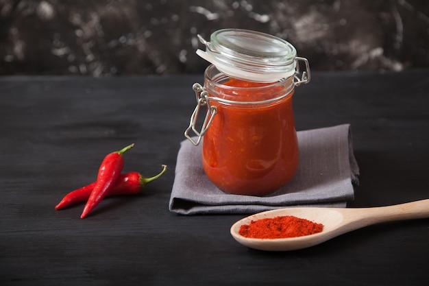 Il condimento piccante di harissa in un barattolo di vetro si trova su un tovagliolo di lino grigio, un cucchiaio di legno con spezie e peperoncino.