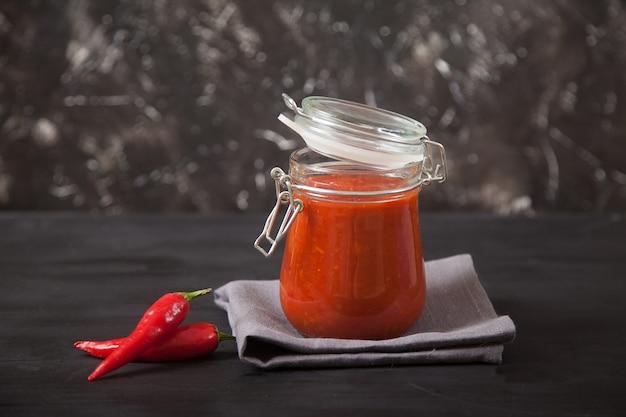 Condimento piccante harissa in un barattolo di vetro con coperchio e peperoncino.