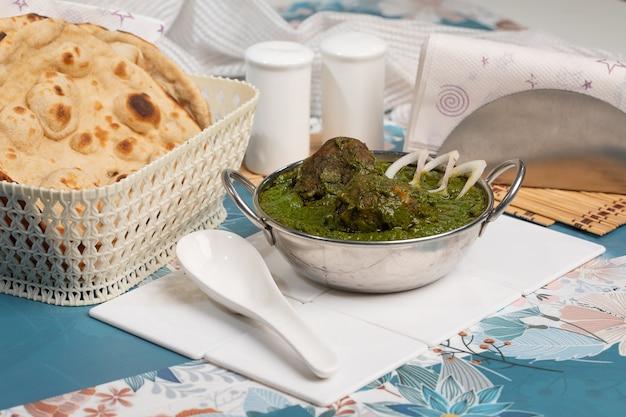 Hariyali kofta curry in ciotola a sfondo bianco ardesia. hariyali kofta è un piatto di cucina indiana con patate e formaggio paneer fritte polpette in salsa di pomodoro cipolla con spezie. cibo indiano.