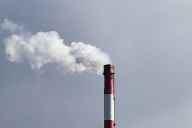 Evaporazione dannosa da un tubo. camino della fabbrica con fumo bianco e cielo contaminato